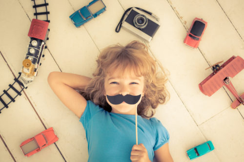 Hipster kid with vintage wooden toys at home. Girl power and feminism concept